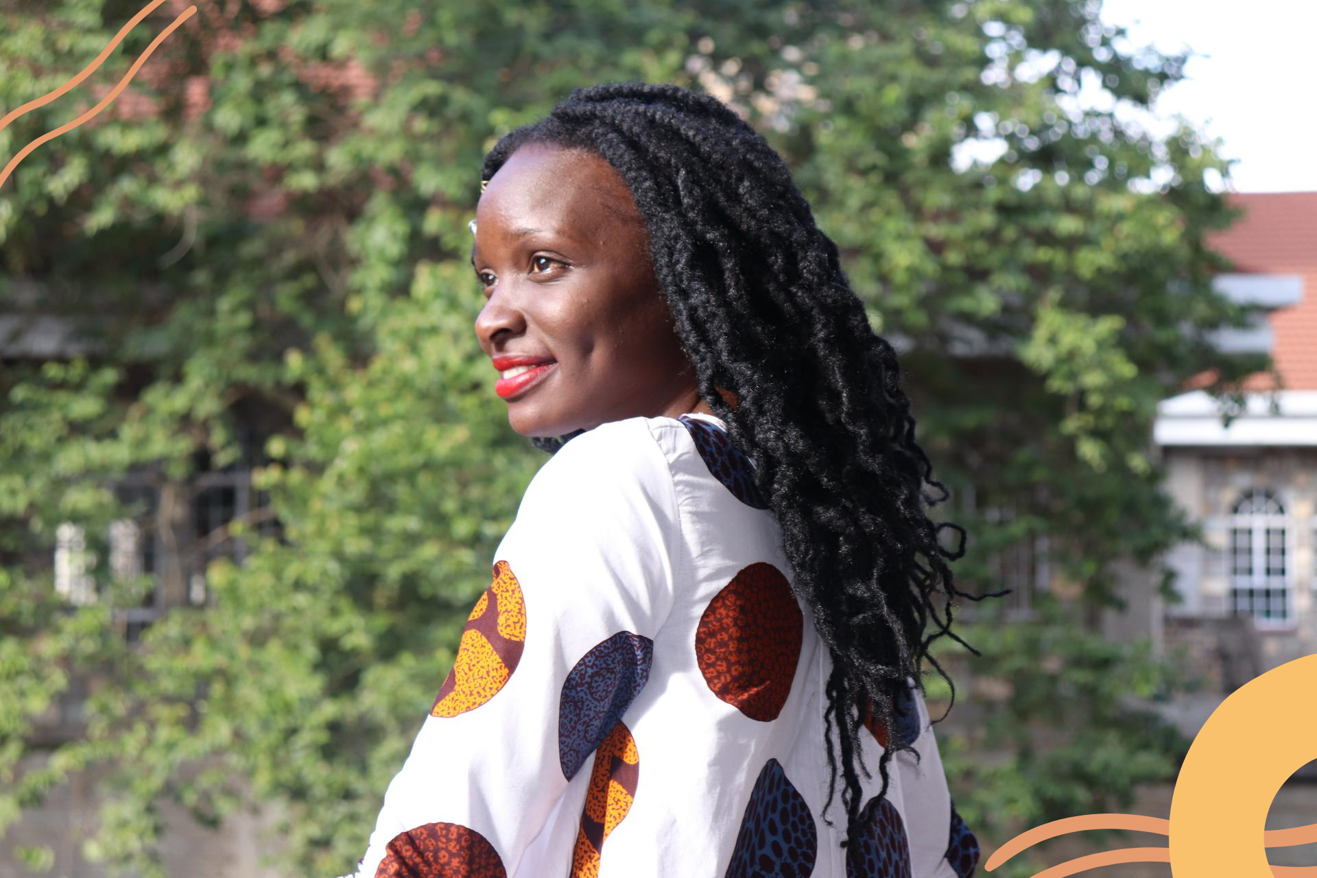 Image of a black woman wearing red lipstick, she smiles off camera and the sun hits her face.